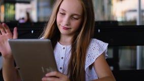 Junges Mädchen, das Spiele auf Tabletten-PC im Café verwendet und spielt stock footage