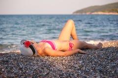 Junges Mädchen, das am Strand mit Hut aufwirft Stockfotos