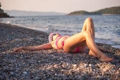 Junges Mädchen, das am Strand mit Hut aufwirft Lizenzfreie Stockfotografie