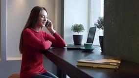 Junges Mädchen, das am Telefon in einem Café spricht stock video footage