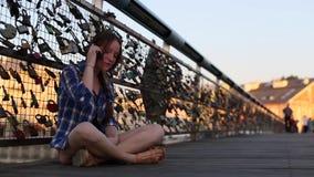 Junges Mädchen, das am Telefon sitzt auf einer Fußgängerbrücke spricht stock footage