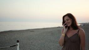 Junges Mädchen, das am Telefon am Strand spricht stock footage