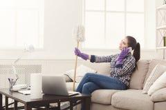Junges Mädchen, das am Telefon während der Reinigung spricht lizenzfreie stockfotografie