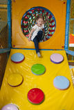 Junges Mädchen, das unten Rampe in der weichen Spielmitte klettert Stockbilder