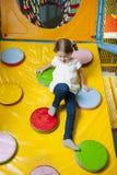 Junges Mädchen, das unten Rampe in der weichen Spielmitte klettert Stockfoto