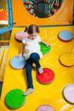 Junges Mädchen, das unten Rampe in der weichen Spielmitte klettert Lizenzfreies Stockfoto