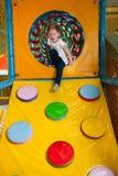 Junges Mädchen, das unten Rampe in der weichen Spielmitte klettert Stockfotografie