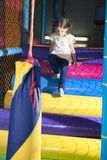 Junges Mädchen, das unten Spielturnhalle klettert Stockfoto