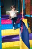 Junges Mädchen, das unten Spielturnhalle klettert Stockbild