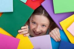 Junges Mädchen, das unter von den Büchern auftaucht Lizenzfreie Stockfotografie
