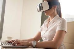 Junges Mädchen, das VR-Kopfhörer trägt und auf Laptop schreibt Stockfotos