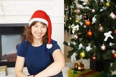 Junges Mädchen, das Weihnachtsbaum sitzt Stockfoto