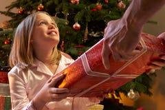 Junges Mädchen, das Weihnachtsgeschenk empfängt Stockfoto