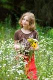 Junges Mädchen, das wilde Blumen auswählt Stockbilder