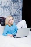 Junges Mädchen, das zu Hause auf Bett mit Laptop sitzt Lizenzfreie Stockbilder