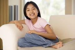 Junges Mädchen, das zu Hause auf einem Sofa sitzt Stockbild