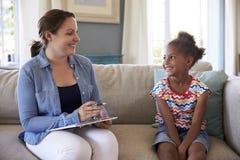 Junges Mädchen, das zu Hause mit Ratgeber spricht Stockfoto
