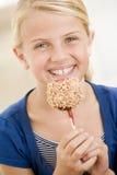 Junges Mädchen, das zuhause Süßigkeitapfel isst Stockfoto