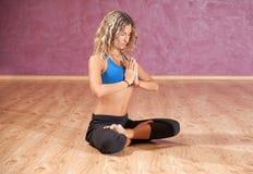 Junges Mädchen, das zuhause Yoga auf Matte tut Stockfotografie
