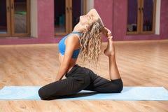 Junges Mädchen, das zuhause Yoga auf Matte tut Stockfoto
