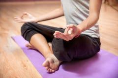 Junges Mädchen, das zuhause Yoga in der Nahaufnahme des Lotussitzes tut Lizenzfreies Stockfoto