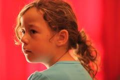 Junges Mädchen, das zur Seite im roten Hintergrund schaut Lizenzfreies Stockbild