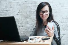 Junges Mädchen in den Gläsern, mit Kunden am Telefon, sprechend emotionales Porträt des Blogger, Stockbilder