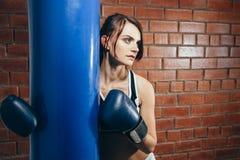Junges Mädchen in den Handschuhen, die nach einem Training in der Verpackenturnhalle stillstehen Stockfotos