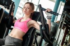 Junges Mädchen in den Sporthandschuhen im gesunden Lebensstil der Turnhalle, der auf der Maschine hält die Griffe stillstehen sit lizenzfreie stockfotos