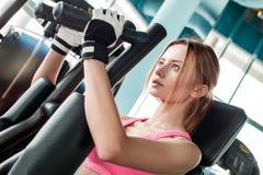 Junges Mädchen in den Sporthandschuhen im gesunden Lebensstil der Turnhalle, der auf Maschinenholding sitzt, behandelt durchdacht lizenzfreies stockfoto