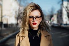 Junges Mädchen der Mode in den Gläsern Blonde, rote Lippen, beige Mantel, der entlang die Stadtstraße geht Lizenzfreie Stockbilder
