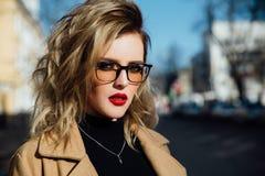 Junges Mädchen der Mode in den Gläsern Blonde, rote Lippen, beige Mantel, der entlang die Stadtstraße geht Stockbild