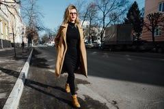 Junges Mädchen der Mode in den Gläsern Blonde, rote Lippen, beige Mantel, der entlang die Stadtstraße geht Stockfoto