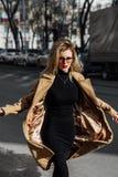 Junges Mädchen der Mode in den Gläsern Blonde, rote Lippen, beige Mantel, der entlang die Stadtstraße geht Lizenzfreies Stockfoto