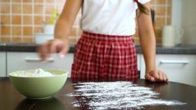 Junges Mädchen der Nahaufnahme übergibt das Vorbereiten der Aufspannfläche für knetendes ausgebreitetes Mehl des Teigs auf dunkle stock video
