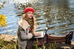 Junges Mädchen in der roten Kappe studiert in der Natur mit Laptop lizenzfreie stockfotos