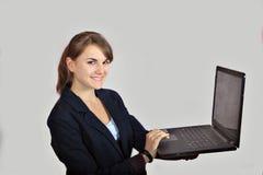 Junges Mädchen der Rothaarigen arbeitet an einem Laptop, der auf grauem Hintergrund lokalisiert wird stockbild