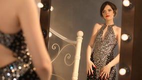 Junges Mädchen der schönen Mode im eleganten schwarzen Kleid mit Make-up und Frisur, attraktiver Brunette, der vor aufwirft stock video