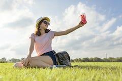 Junges Mädchen in der Sonnenbrille und Hutgetränksommerbeerengetränk mit dem Eis, das auf grünem Gras, Kopienraum, goldene Stunde stockbild