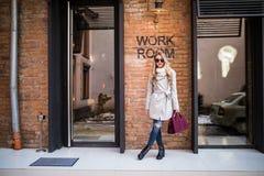Junges Mädchen in der stilvollen Sonnenbrille und mit einer modernen Tasche am Arbeitsgebäude Stockfoto