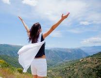 Junges Mädchen in der weißen Kleidung, die auf Felsen in Griechenland steht lizenzfreie stockfotos