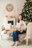 Junges Mädchen in der weißen Strickjacke, die Welpe Waliser-Corgi-Wolljacke streicht stockfotos