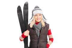 Junges Mädchen in der Winterkleidung, die Skis hält Lizenzfreie Stockfotos