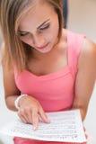 Junges Mädchen des hübschen Musikers liest stockbilder