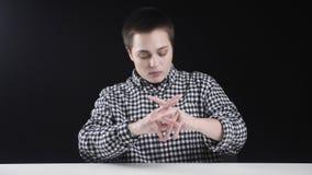 Junges Mädchen des kurzen Haares, das ihre Arme und Hals, Sportkonzeption, schwarzer Hintergrund aufwärmt stock video
