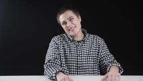 Junges Mädchen des kurzen Haares hört auf Witz und lacht, Kommunikationskonzept, schwarzer Hintergrund stock footage