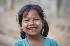 Junges Mädchen des Porträts mit thanaka auf ihrem Lächelngesicht Mrauk U, Myanmar Lizenzfreie Stockfotografie