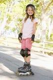 Junges Mädchen draußen auf dem Inline-Rochenlächeln Lizenzfreies Stockbild