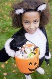 Junges Mädchen draußen in der Katzekostüm-Holdingsüßigkeit Stockfoto