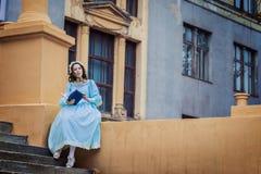 Junges Mädchen in einem blauen Weinlesekleid liest eine Liebesgeschichte stockbild